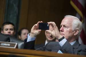 """UNITED STATES - SEPTEMBER 26: Sen. John Cornyn, R-Texas, takes a picture during a Senate Judiciary Committee hearing titled """"Special Counsels and the Separation of Powers,"""" on September 26, 2017. (Photo By Tom Williams/CQ Roll Call)"""