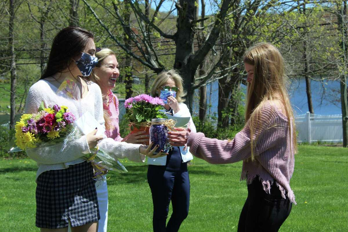 Brooke's sister Riley and mother Madeline, left, accept flowers and a jar of purple M&M's from Nutmeg Chapter member Ashley Gotti, right. Purple was Brooke's favorite color.