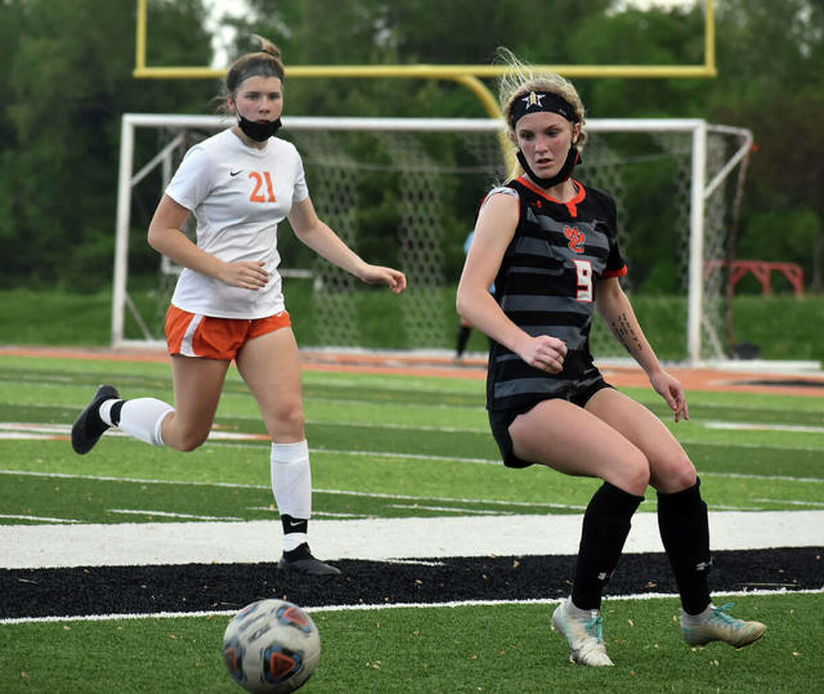 Edwardsville's Payton Federmann, right, prepares to play the ball near the sideline during the second half of Monday's game against Waterloo inside the District 7 Sports Complex.