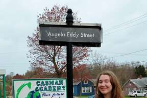Angela Eddy, the CASMAN Academy Student of the Month, poses next to the sign that names the school driveway in her honor. (Courtesy photo)