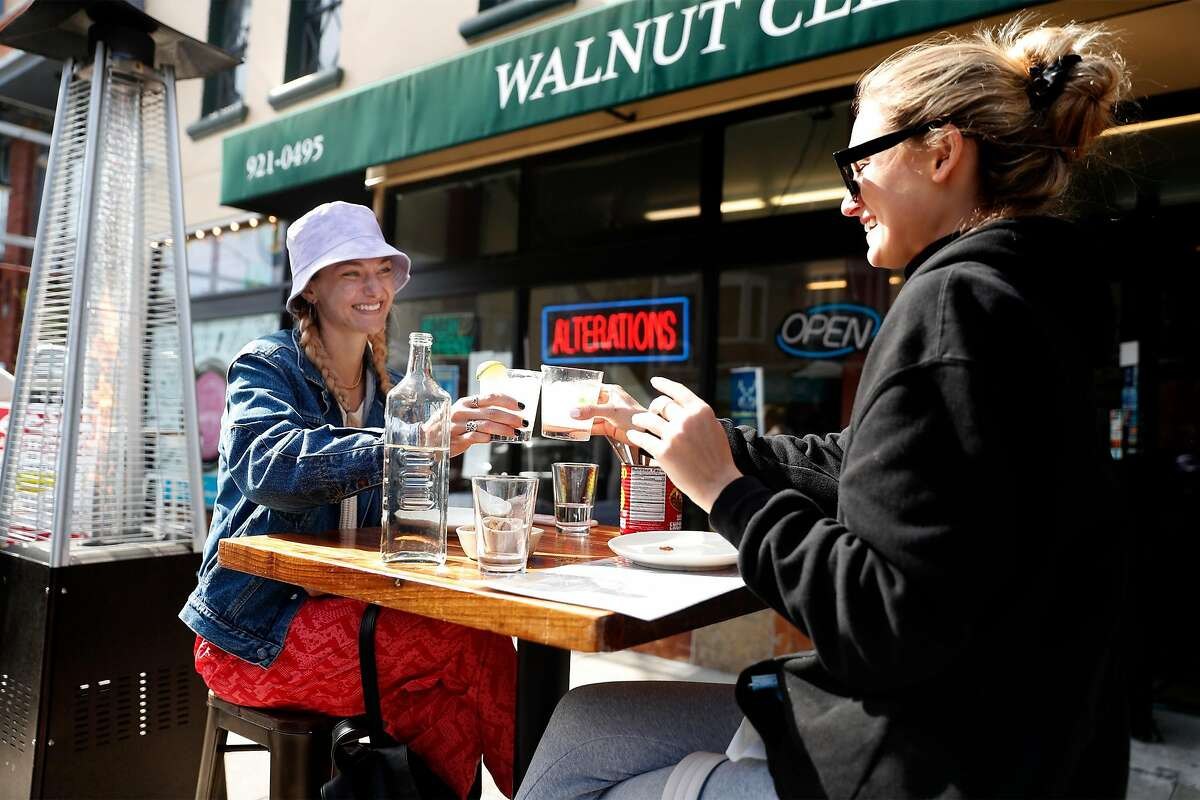 Katie and Kelly (last names not given) toast each other as they enjoy margaritas at Rolo on Chestnut Street in San Francisco, Calif., on Thursday, April 29, 2021. San Francisco is on track to gain entry to the yellow tier of California's pandemic restrictions.