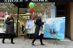 Folks walk past paintings by Janice Lockhart, left, and Kate Moran outside Shoes 'N' More during the Art to the Avenue event along Greenwich Avenue in Greenwich, Conn. Thursday, May 2, 2019.