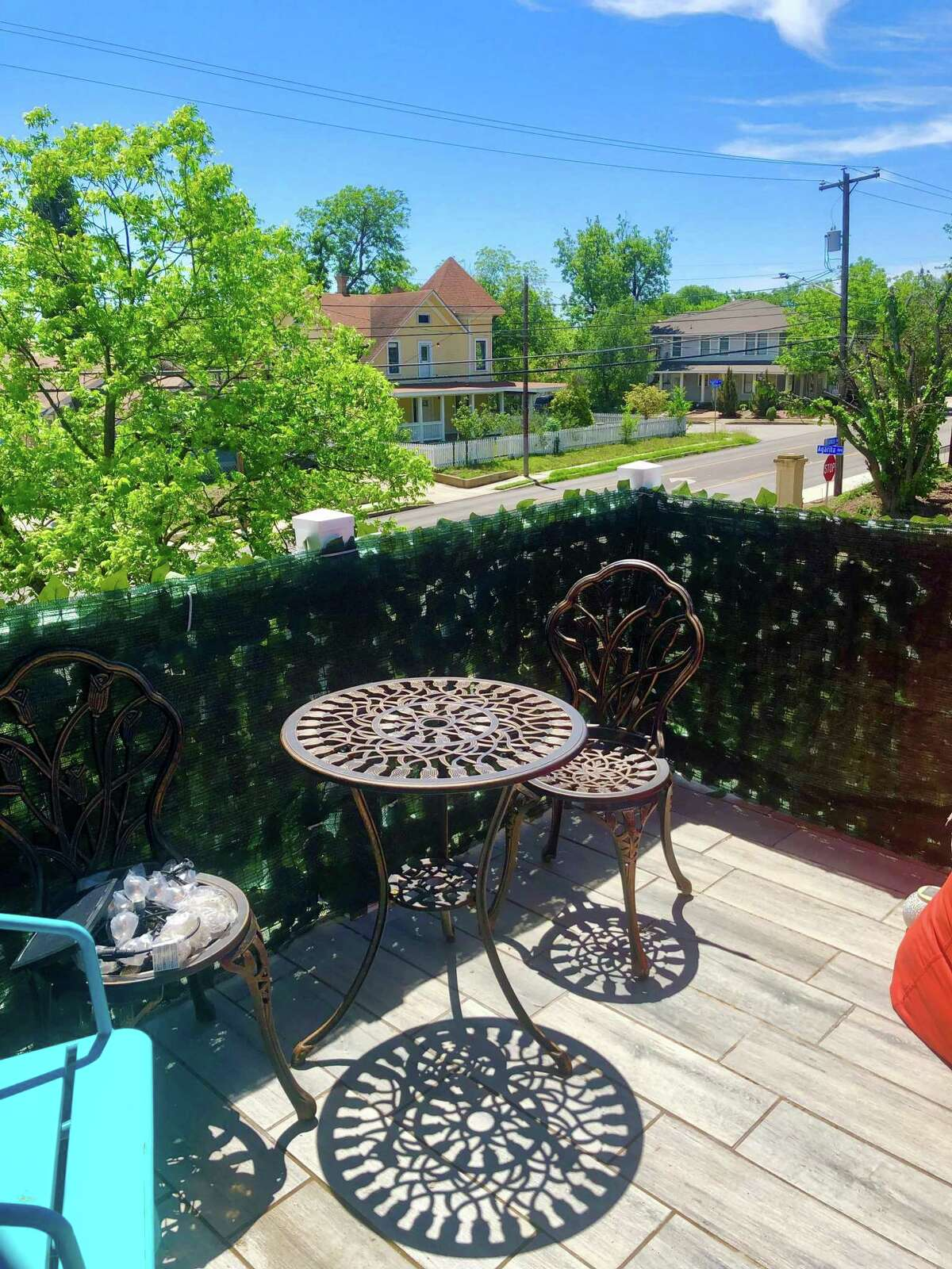 The rebuilt balcony off the master bedroom provides a pleasant outdoor seating area with a ceramic tile floor and fake ivy added to the surrounding railing for privacy.