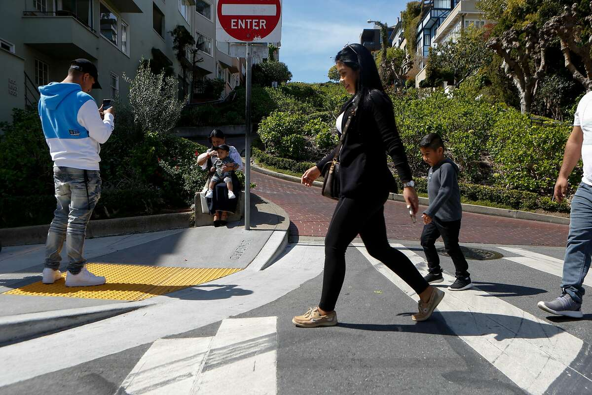 A few tourists walk by and snap photos at a nearly empty Lombard Street in March in San Francisco.