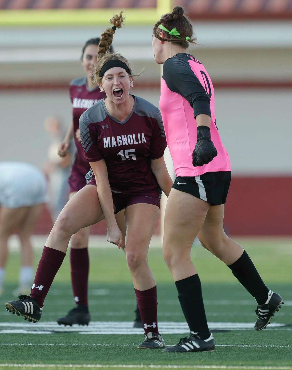 Magnolia's Skyler Replogle (15) jokes with goalie Taylor Sanderson (0) before the first period of a bi-district high school soccer match, Friday, March 26, 2021, in Waller.