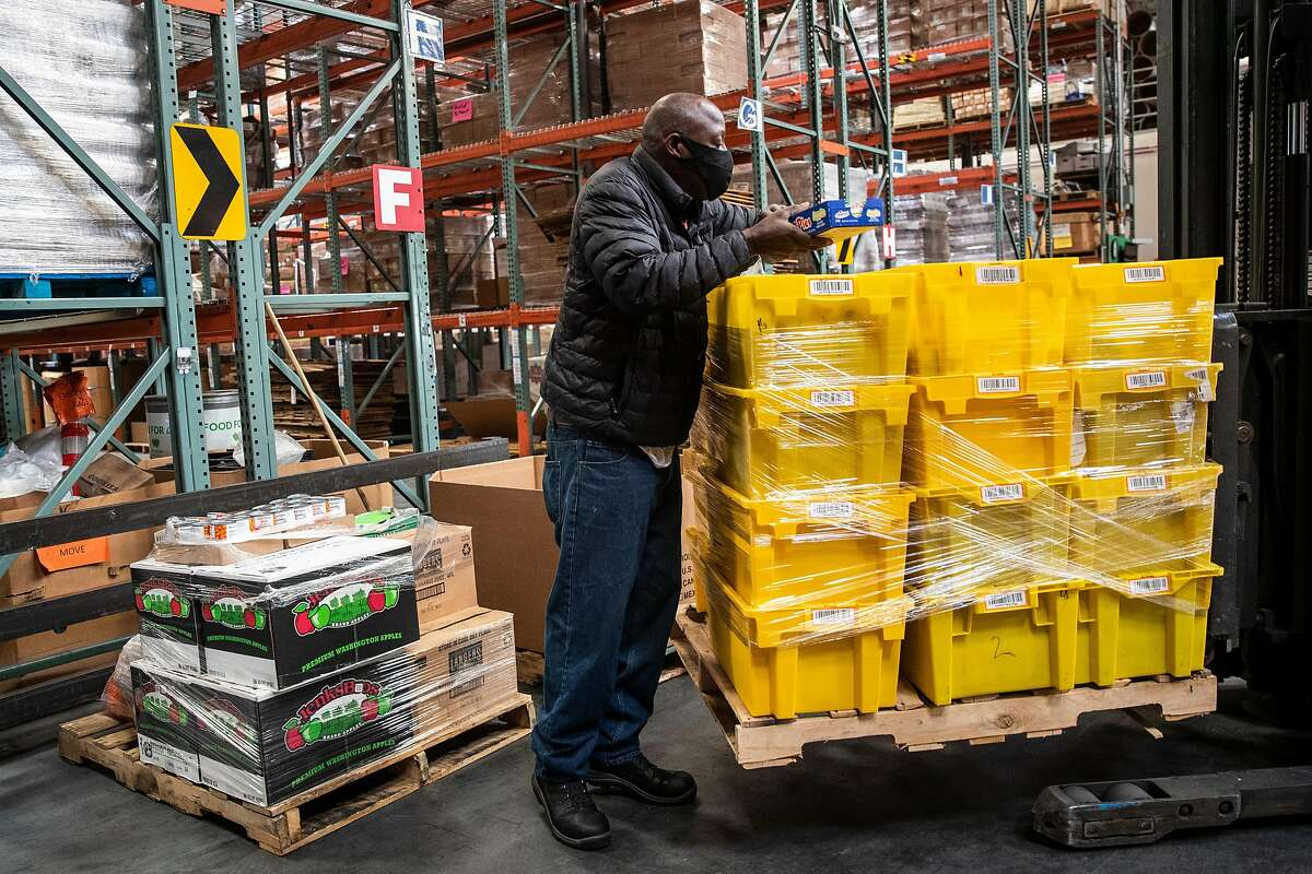 Henry Randolph, shop floor manager at the S.F.-Marin Food Bank, sorts a pallet of new donations Monday.