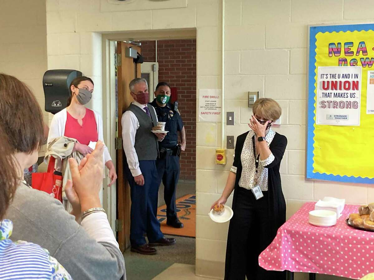 East Ridge Middle School band teacher Hilary Brown wipes away tears while addressing colleagues at a surprise teacher appreciation breakfast on May 3.