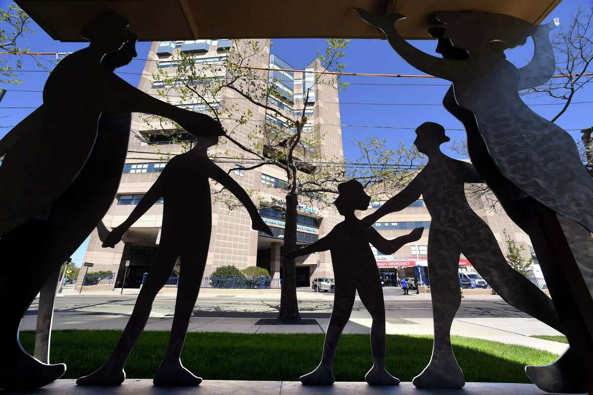 Yale New Haven Children's Hospital can be seen in the background through a silhouetted sculpture at the Ronald McDonald House of Connecticut in New Haven on May 13, 2020.