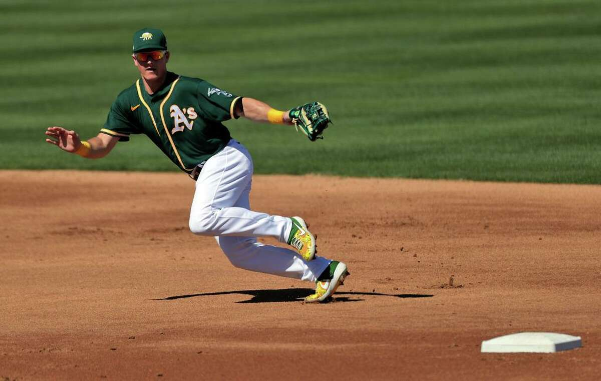 A's third baseman Matt Chapman runs back to cover third from near second in a defensive shift while playing the Los Angeles Angels during a spring training game at Hohokam Stadium in Mesa, Ariz., on Friday, March 5, 2021.