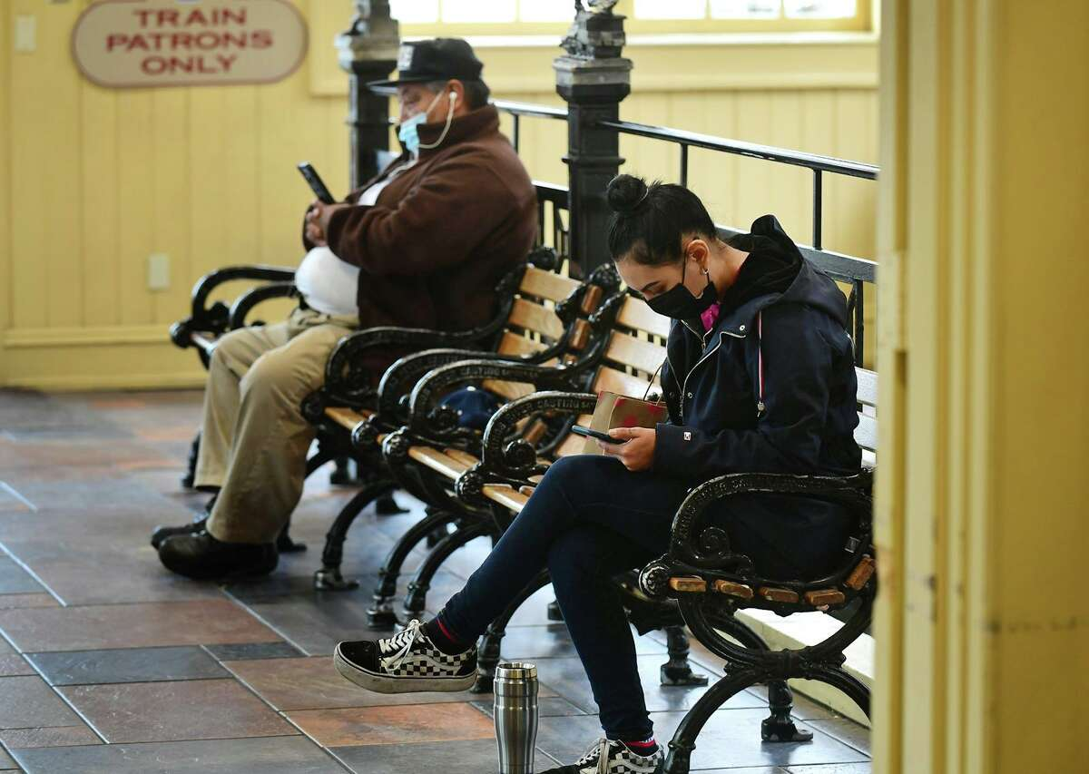 Commuters use their cellphones at the South Norwalk train station Tuesday, May 4, 2021, in Norwalk, Conn.