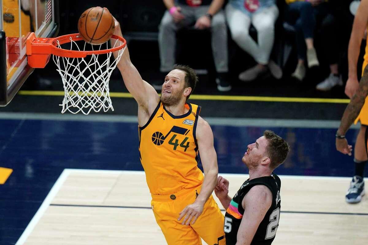 Utah Jazz forward Bojan Bogdanovic (44) dunks on San Antonio Spurs center Jakob Poeltl (25) in the first half during an NBA basketball game Monday, May 3, 2021, in Salt Lake City. (AP Photo/Rick Bowmer)
