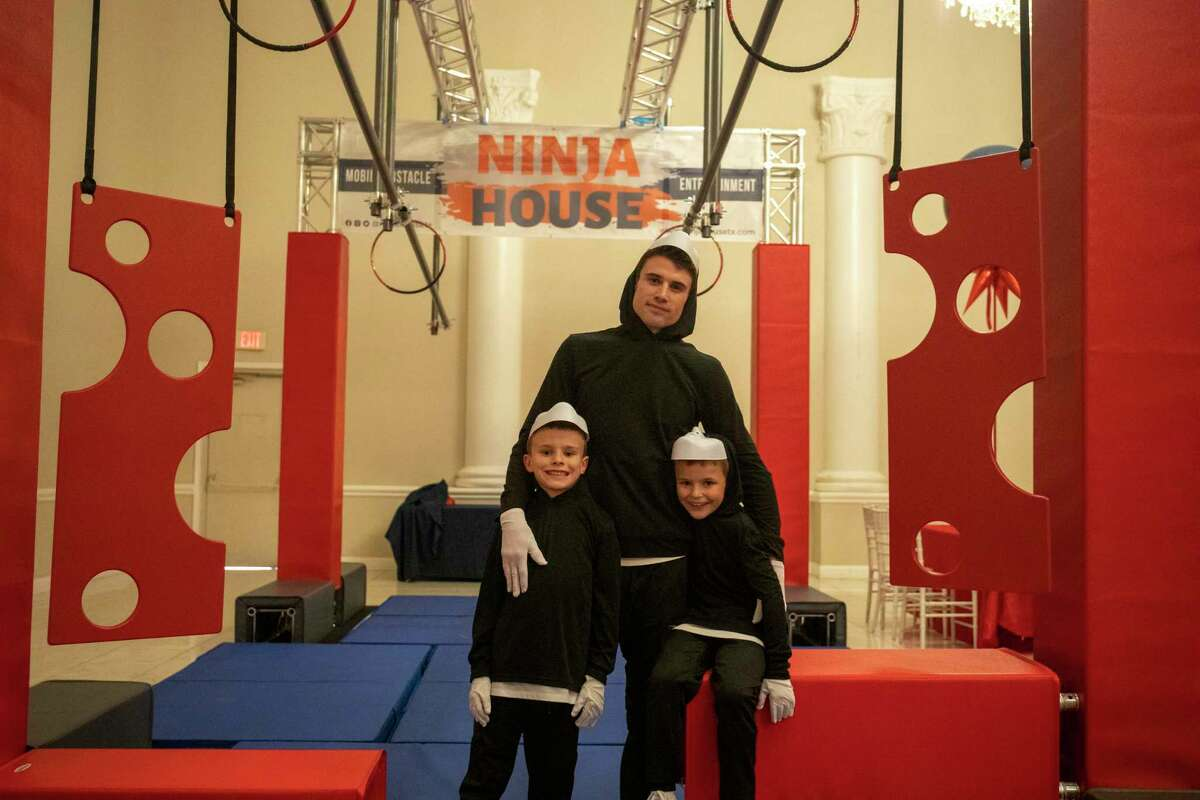 Ross Klabon, center, with his twin sons Connor, right, and Collin, left, pose in front of the Ninja House obstacle course Friday, April 30, 2021 set up at the Cuthbert Mansion. Jacy Lewis/Reporter-Telegram
