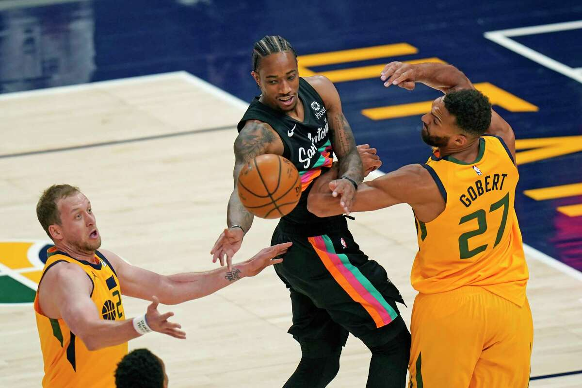 San Antonio Spurs forward DeMar DeRozan, center, passes the ball as Utah Jazz's Joe Ingles (2) and Rudy Gobert (27) defend in the first half during an NBA basketball game Monday, May 3, 2021, in Salt Lake City. (AP Photo/Rick Bowmer)