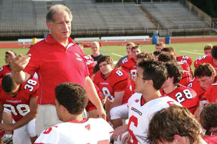Greenwich High School head football coach Rich Albonizio speaks with his players after a practice session earlier this season. Photo: David Ames, Greenwich Time