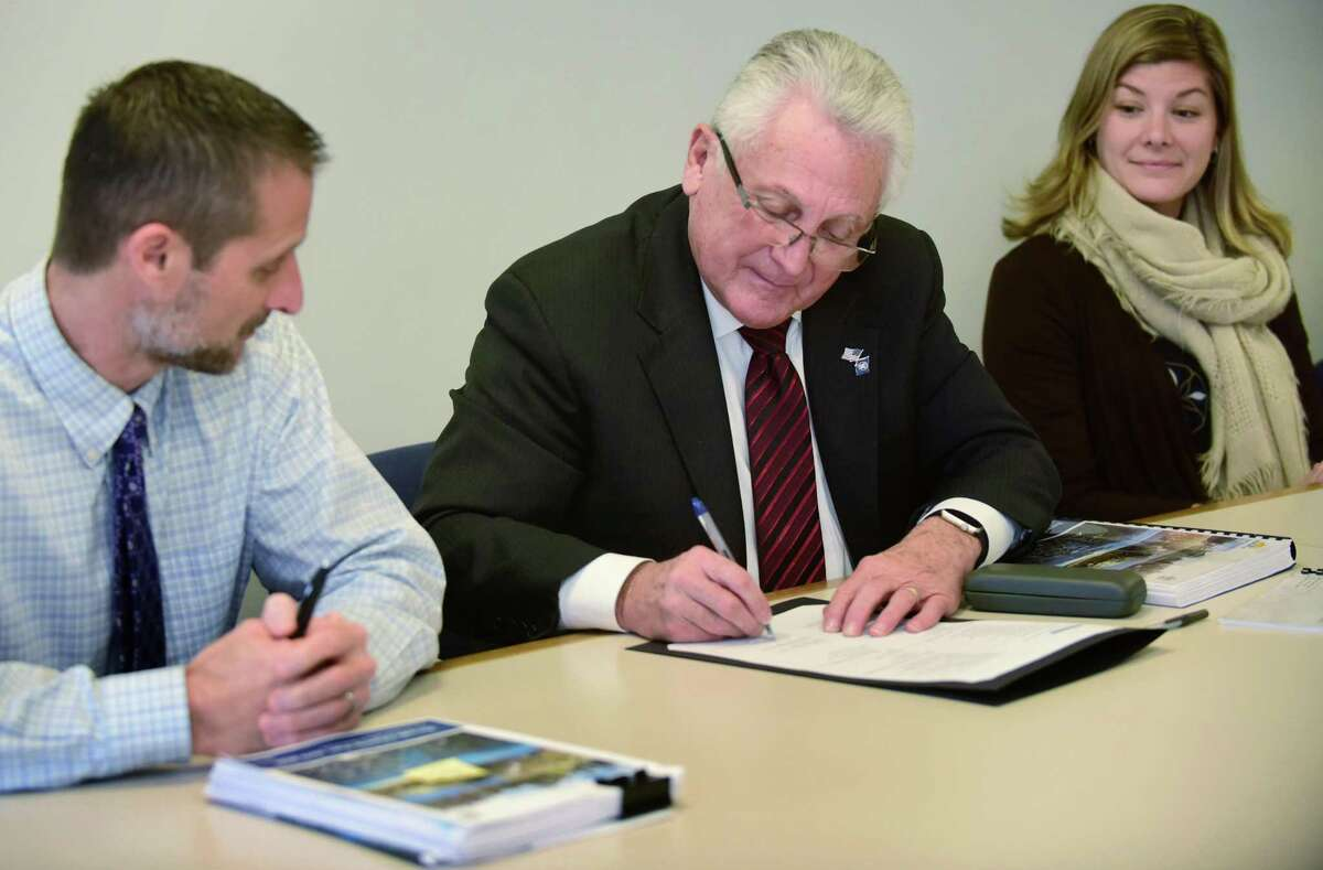 Norwalk Mayor Harry Rilling, center, signs the city's new Plan of Conservation and Development with Planning and Zoning Director Steve Kleppin, left, Norwalk Chief of Economic and Community Development, Jessica Casey, right, and the rest of the POCD committee including Planning and Zoning Director Steven Kleppin, left, Thursday, December 5, 2019, at City Hall in Norwalk, Conn. The plan will guide development in the city from 2019 to 2029.