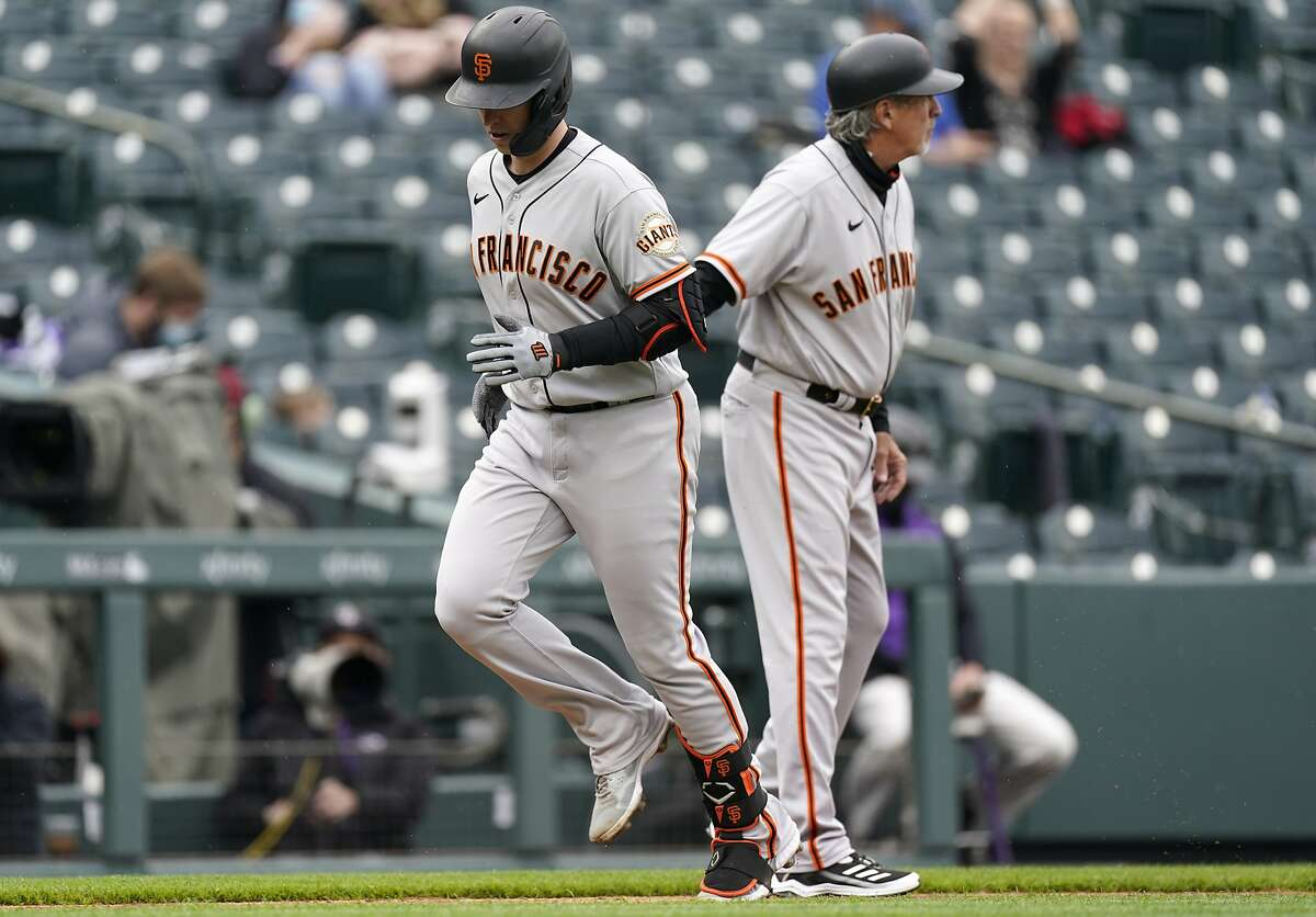 San Francisco Giants' Buster Posey, front, is congratulated by third base coach Ron Wotus while circling the bases after hitting a solo home run in the first inning of game one of a baseball doubleheader Tuesday, May 4, 2021, in Denver. (AP Photo/David Zalubowski)