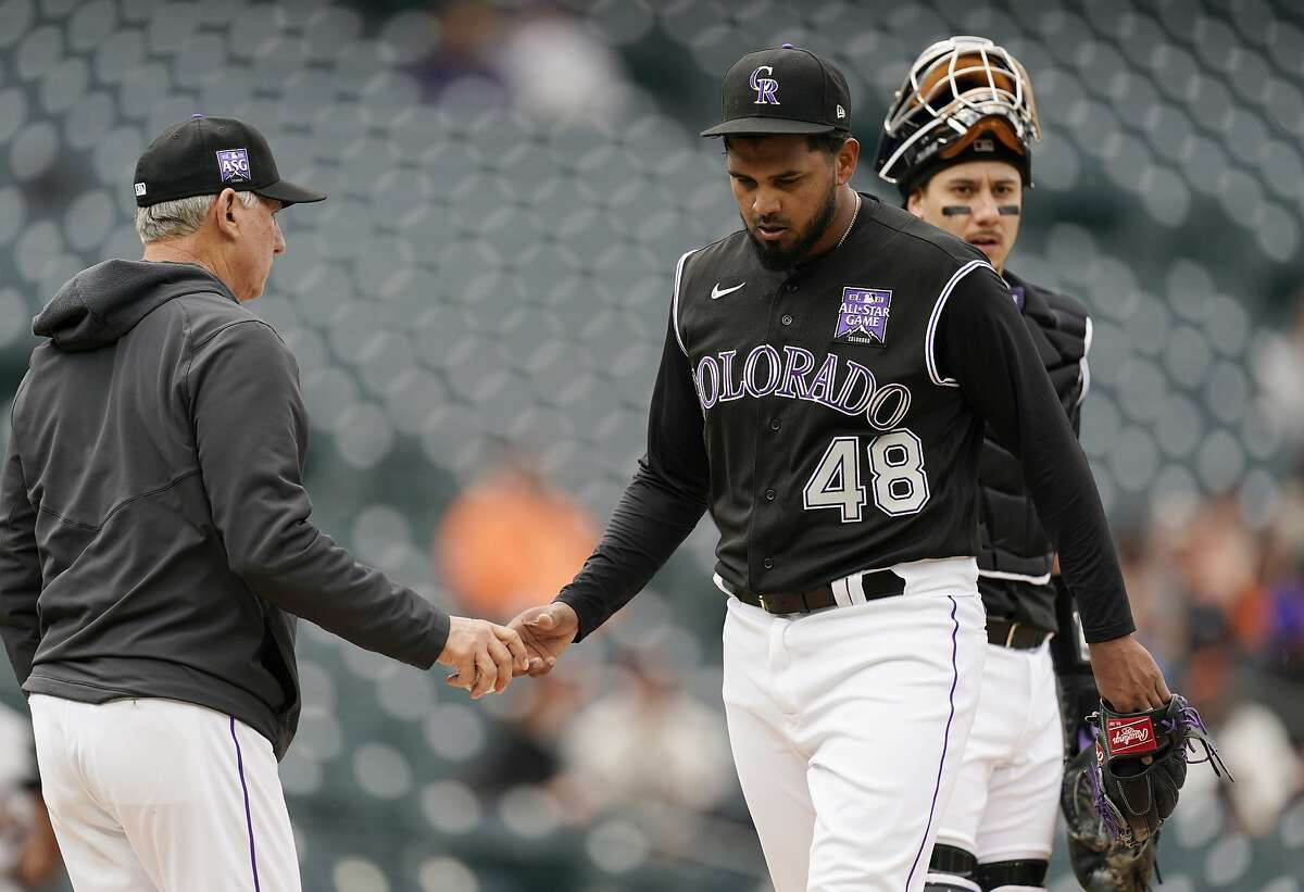 Colorado Rockies starting pitcher German Marquez, right, hands the ball to manager Bud Black as Marquez is pulled from the mound after walking San Francisco Giants' Mike Tauchman in the first inning of game one of a baseball doubleheader Tuesday, May 4, 2021, in Denver. (AP Photo/David Zalubowski)