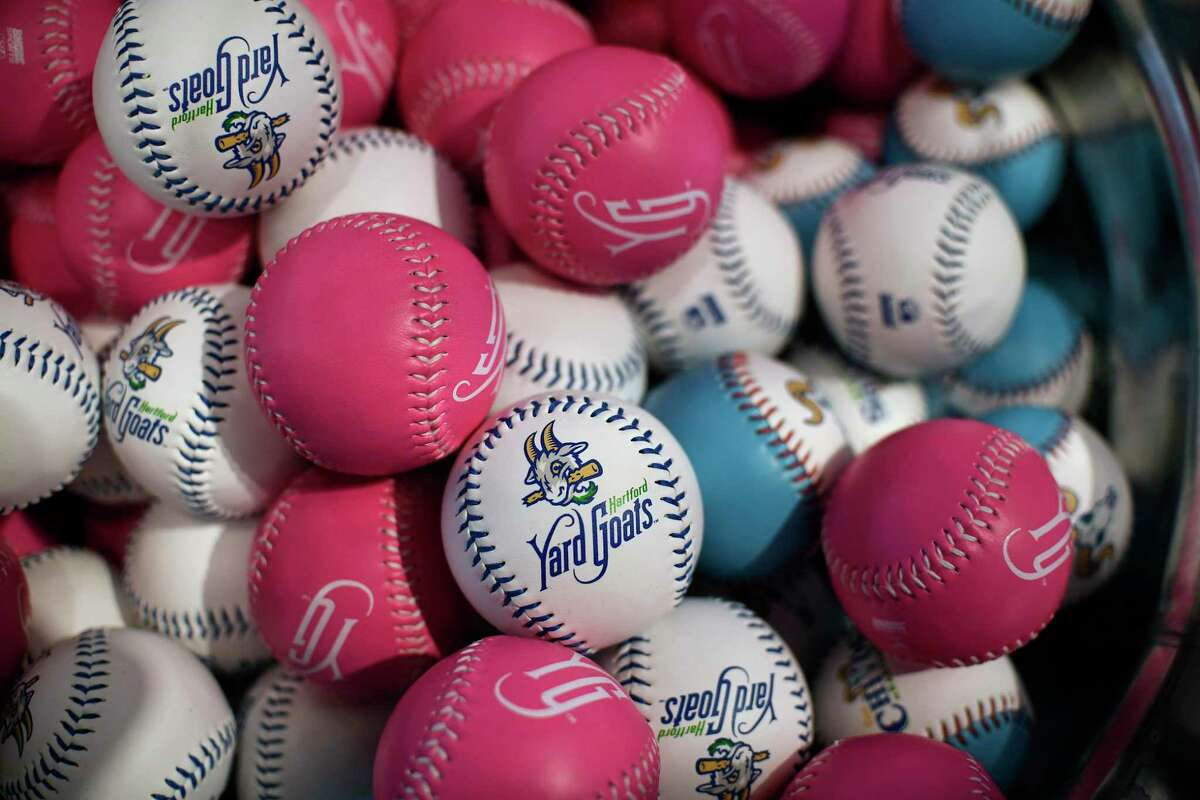 Hartford Yard Goats souvenir baseballs are displayed for sale in a gift shop inside Dunkin' Donuts Park before a game between the Yard Goats and the Richmond Flying Squirrels in Hartford, Conn., on Tuesday, April 16, 2019. Across America, a golden age of minor league baseball branding has unfolded, bursting with exuberance and calibrated localism. (AP Photo/Jessica Hill)