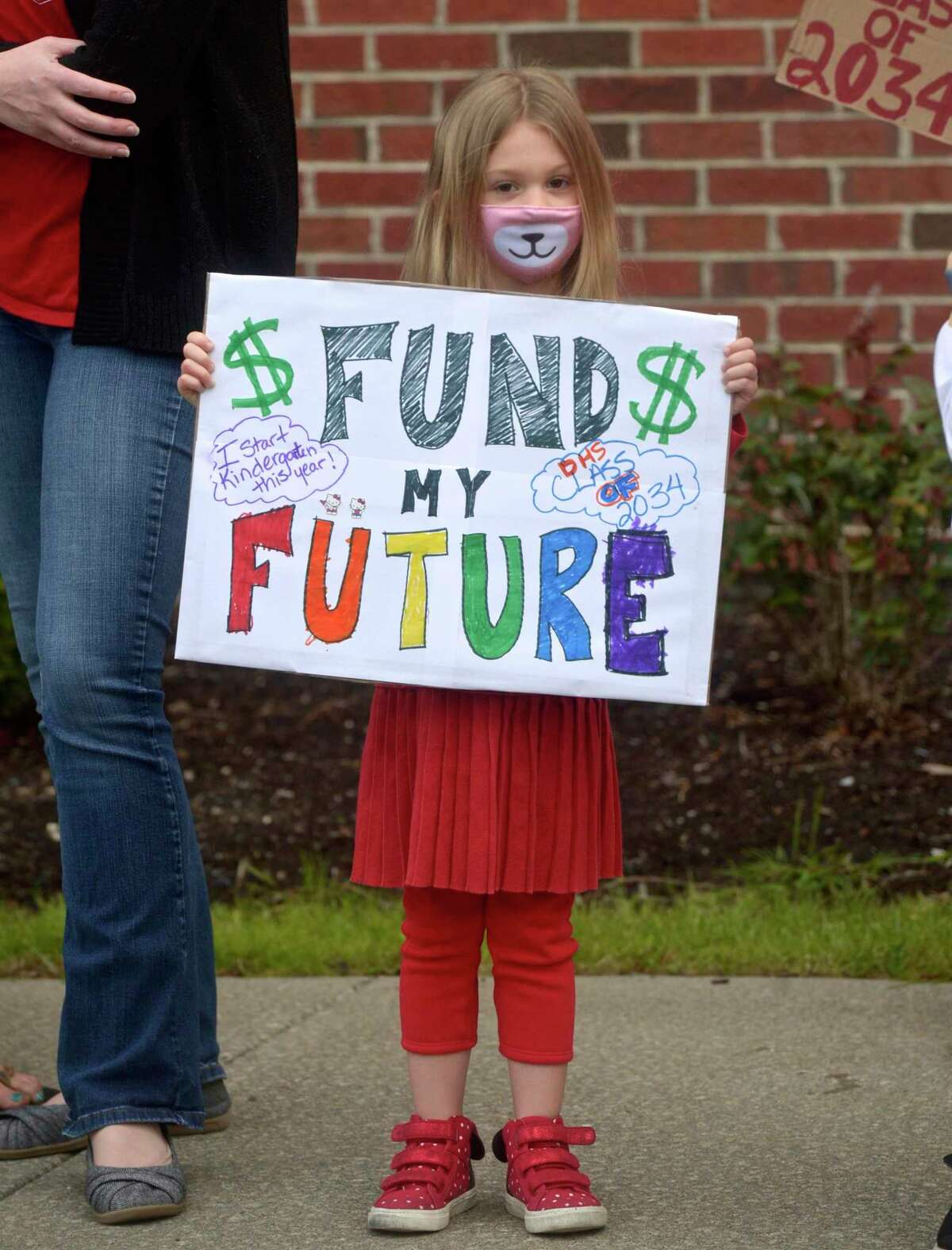 Gloria Saunders, age 5, daughter of Rachel Saunders, who works in the middle schools, protested to support city schools along with her mom at City Hall Tuesday. They and other Danbury groups rallied to demand an increase in the school budget. May 4, 2021, in Danbury, Conn.