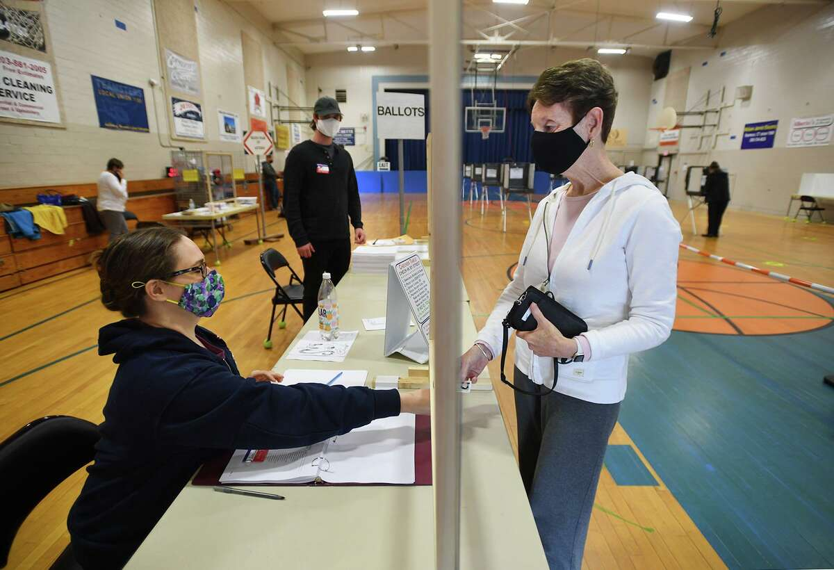 Suzanne Sutherland, right, of Seymour, is checked in to vote by ballot tender Julia Murphy on the town budget referendum at the Seymour Community Center gymnasium in Seymour, Conn. on Tuesday, May 4, 2021.