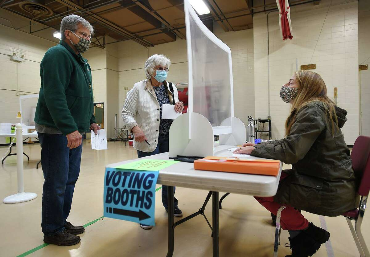Ken and Pat Piddington, of Monroe, check in to vote on the town budget referendum with ballot clerk Ilona Palomba at Masuk High School in Monroe, Conn. on Tuesday, May 4, 2021.