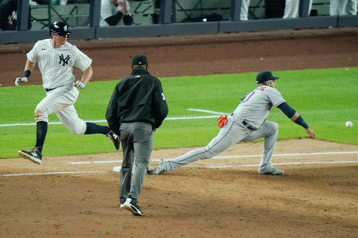 Alex Bregman's throw gets away from Astros first baseman Yuli Gurriel during the sixth inning, when the Yankees scored four times to take control of Tuesday's game.