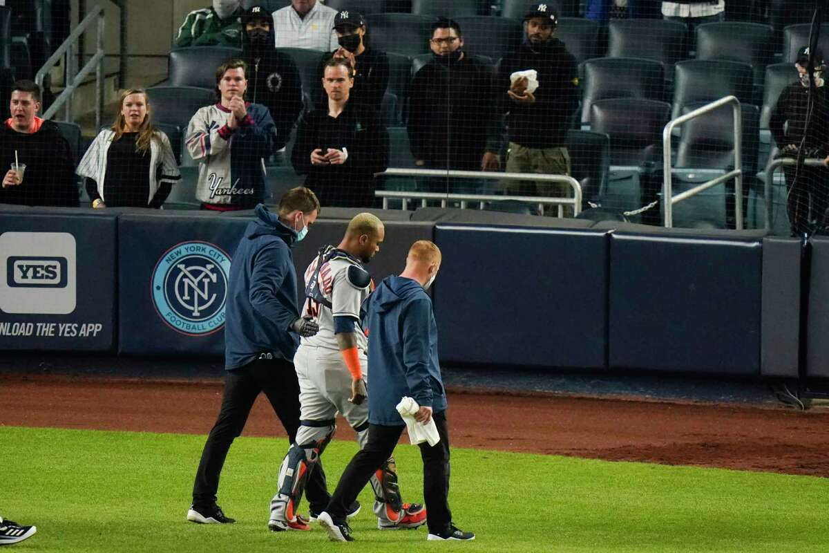 Houston Astros catcher Martin Maldonado is helped off the field after being injured during the sixth inning of a baseball game against the New York Yankees Tuesday, May 4, 2021, in New York. (AP Photo/Frank Franklin II)