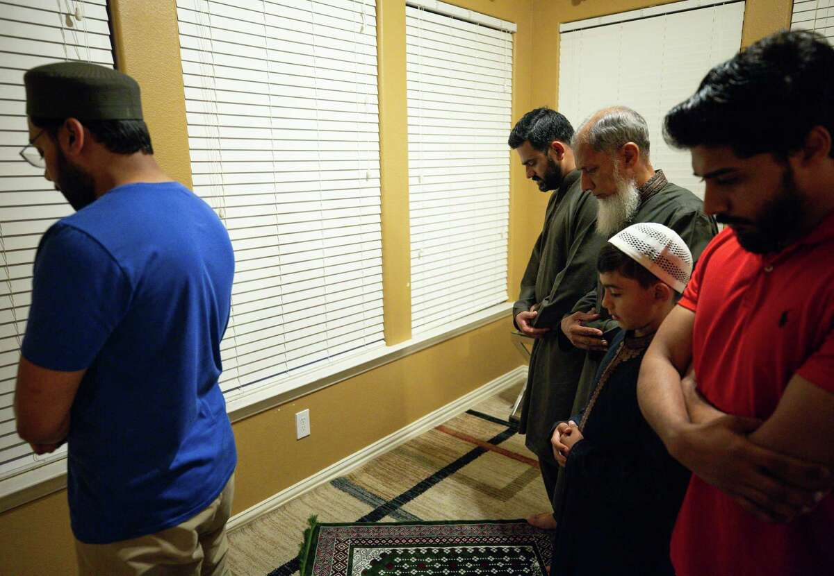 Houston Police Department senior officer Danish Hussain, second from left, and family members gather for Maghrib - or sunset prayer - which follows the breaking of fast during the holy month of Ramadan, on Monday, May 3, 2021, in Texas.