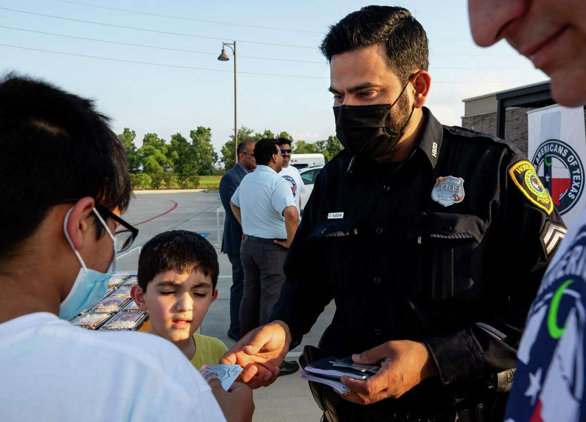 Houston Police Department senior officer Danish Hussain gives away stickers to two boys who were helping out to distribute food to fellow Muslims for Iftar - the meal to break their fast after sunset during the holy month of Ramadan - on Monday, May 3, 2021, in Sugar Land, Texas.