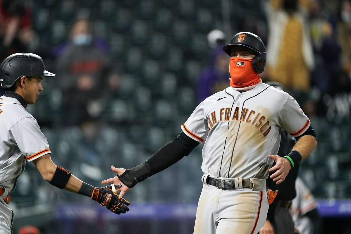 San Francisco Giants' Wilmer Flores, left, congratulates Evan Longoria after they scored on a single hit by Steven Duggar in the fifth inning of game two of a baseball doubleheader against the Colorado Rockies Tuesday, May 4, 2021, in Denver. (AP Photo/David Zalubowski)