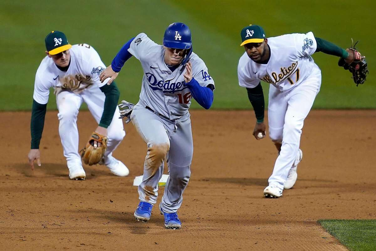 The Dodgers' Will Smith advances after a shift by the A's Matt Chapman (left) and Elvis Andrus left no one at third base.