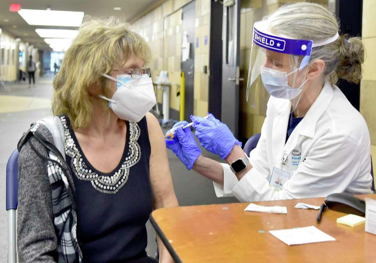 Dr. Soni Clubb vaccinates Jodi Levine, of Hamden, at the Floyd Little Athletic Center.