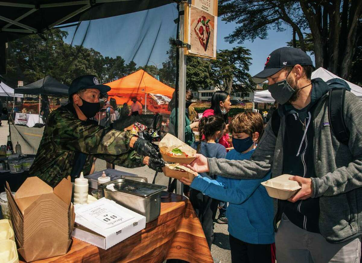 David Lee of Sunset Squares Pizza gives slices to customers at the Outer Sunset Farmers Market & Mercantile in San Francisco.