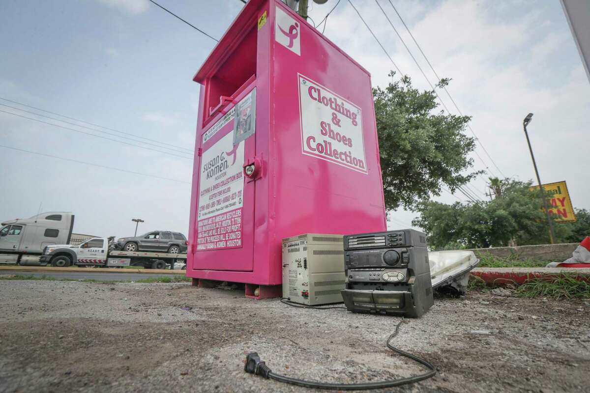 Donated items sit next to a Susan G. Komen for the Cure donation bin at Wilmington St. and Cullen Blvd on Tuesday. City Council on Wednesday unanimously approved a new ordinance to regulate donation bins, including a ban on leaving items outside the bins.