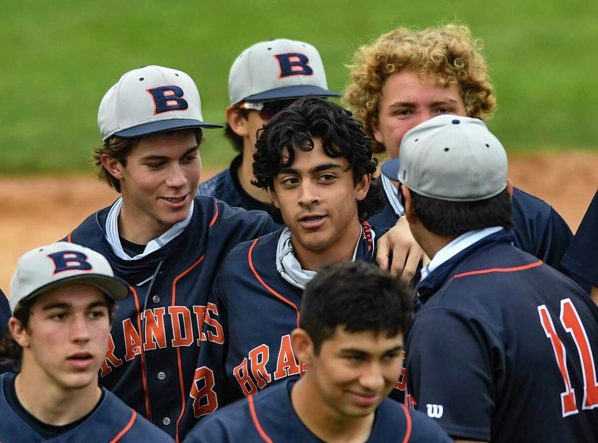 Theodore Falkenberg, middle, is surrounded by teammates after hitting a home run against Brandeis during high-school baseball action at the Blossom Athletic Center on Friday, April16, 2021.