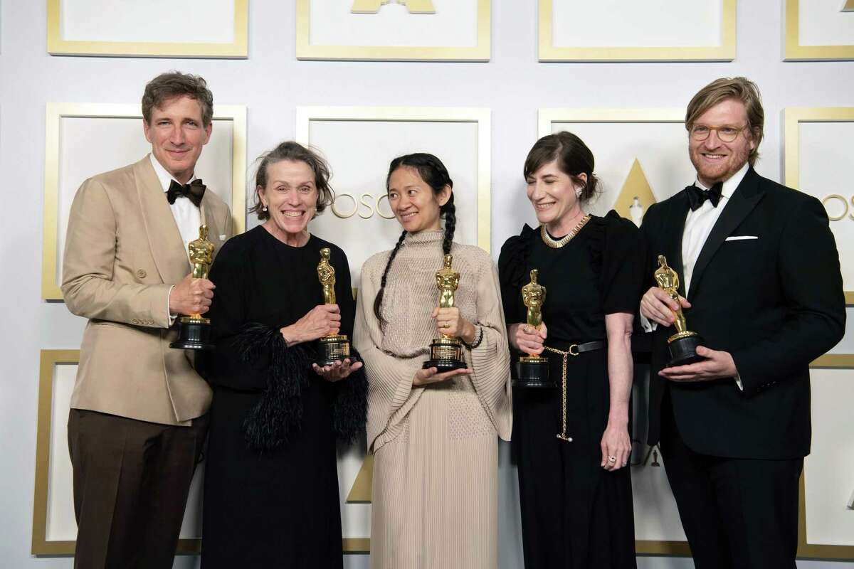 """From left are Peter Spears, Frances McDormand, Chloe Zhao, Mollye Asher, and Wesleyan University graduate Dan Janvey, winners of Best Picture for """"Nomadland."""" They are shown during the 93rd Annual Academy Awards at Union Station April 25 in Los Angeles, California."""