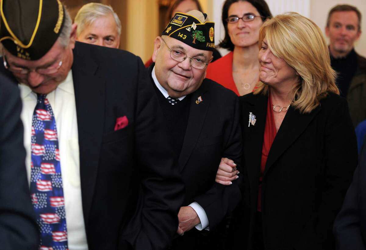 Then-state Rep. Brenda Kupchick smiled at her neighbor, Army veteran Tom Quinn, Wednesday, Nov. 11, 2015, during the annual Veterans Day Ceremony at Old Town Hall in Fairfield, Conn.