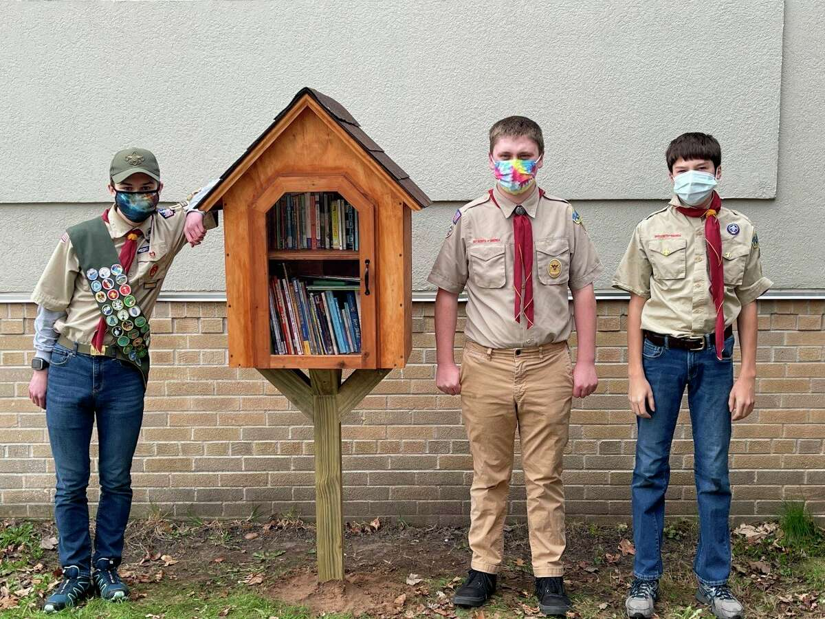 Logan Foster (left) built and installed a little library at Frankfort Elementary School as part of his Eagle Scout project with the help of fellow scouts Chris Kowalewski (middle) and Keith Crompton (right). (Courtesy Photo)