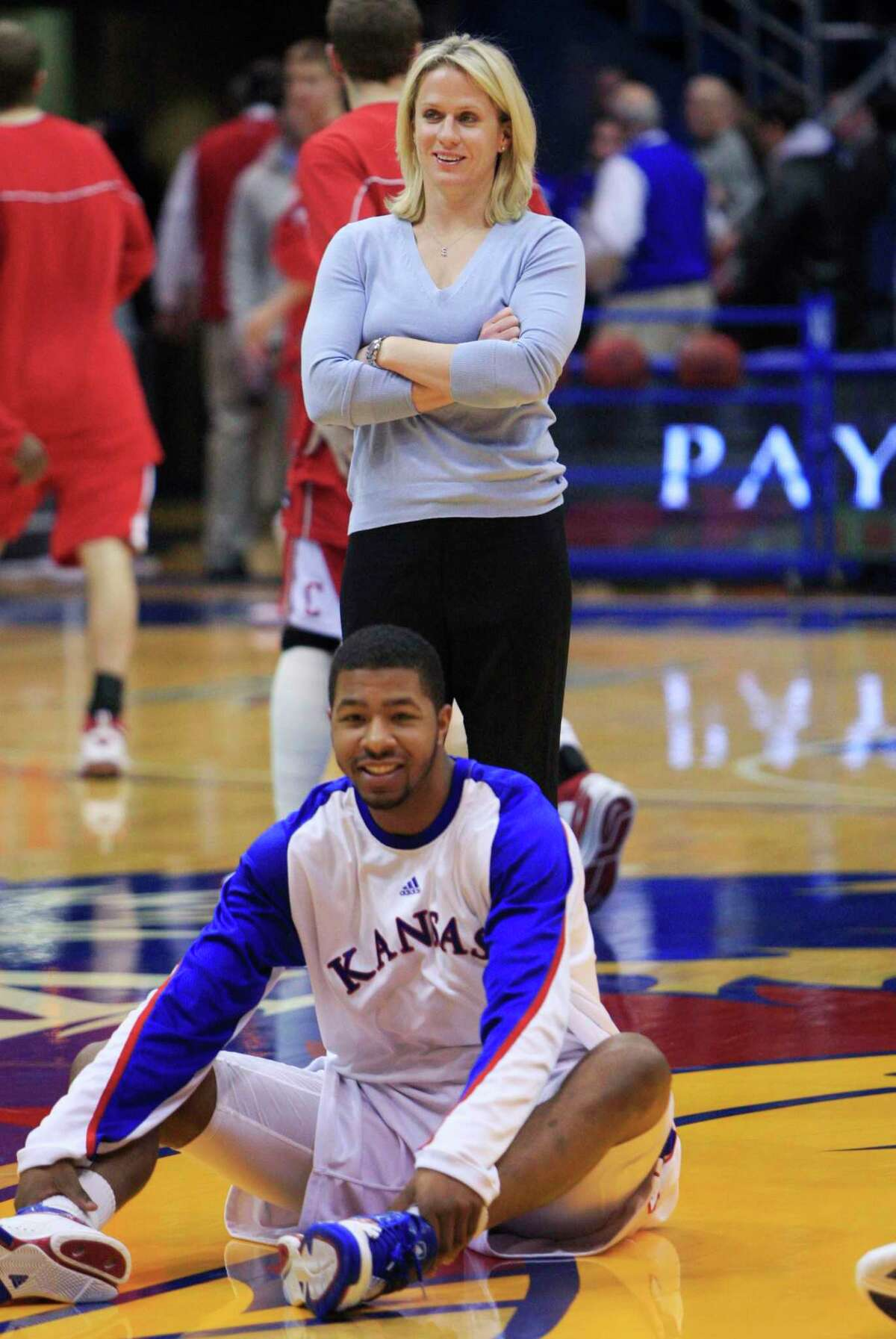 In this Jan. 8, 2010 file photo, Kansas strength coach Andrea Hudy stands behind a Kansas basketball player as they warm up for an NCAA college basketball game against Cornell in Lawrence, Kan. Hudy was named director of sports performance for UConn women's basketball on Wednesday.