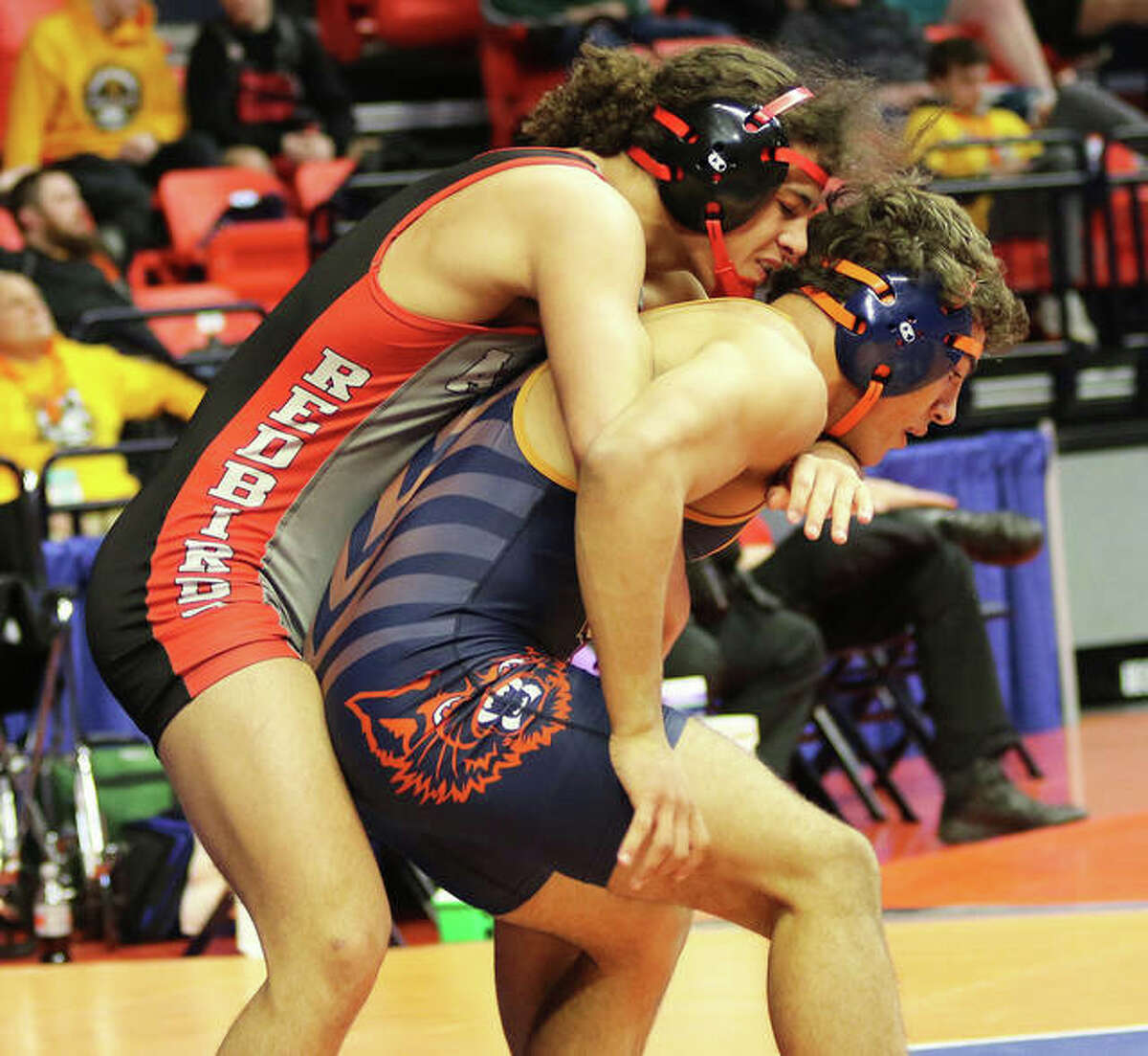 Alton's Damien Jones (left) is one of five returning seniors this season. Jones had a pair of wins at the 2020 IHSA Class 3A State Tournament. Above, he tries to keep Evanston's Ricardo Salinas from escaping during a 170-pound wrestleback at the state tournament at State Farm Center in Champaign.