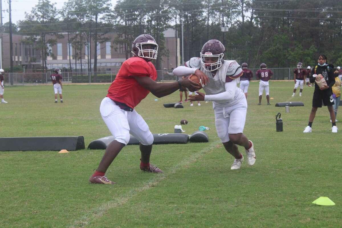 Summer Creek quarterback Jahrik Jones (left) and running back Lloyd Avant (right) working through offensive drills.
