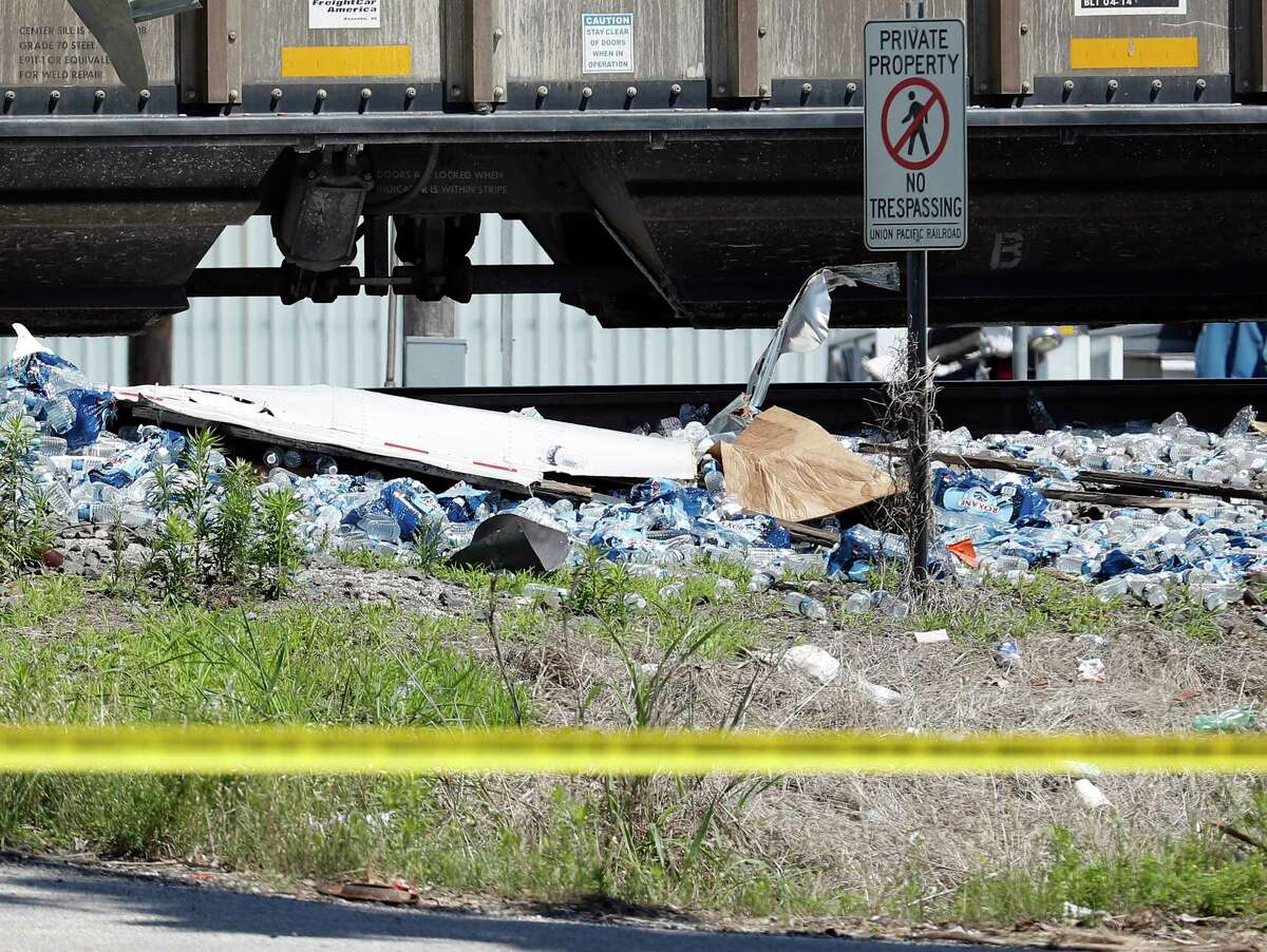 Officials investigate a tractor trailer truck that was struck by a train when his trailer became stuck on the tracks at Second St. and S. Calhoun St, Wednesday, May 5, 2021, in Richmond, Tx. The tractor trailer was carrying bottled water. The driver was not injured.