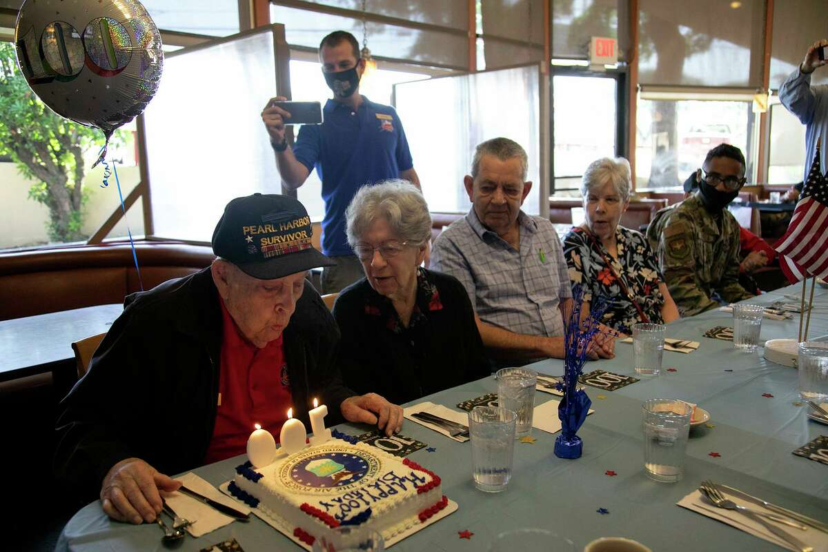Pearl Harbor veteran Kenneth Platt blows out candles for his 100th birthday celebration with family and members of his Alamo Honor Flight monthly breakfast group at a Jim's Restaurant in San Antonio on Wednesday. Joining him, from left, is his wife, Lorena Platt, and their children, Wayne Platt and Linda Branton.