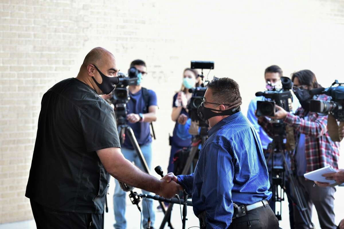 Dr. Umar Khan, left, shakes hands with Balcones Heights Police Sgt. Joey Sepulveda as Sepulveda returned to the Methodist Hospital | Texsan to thank the staff for his care after being wounded in the line of duty.