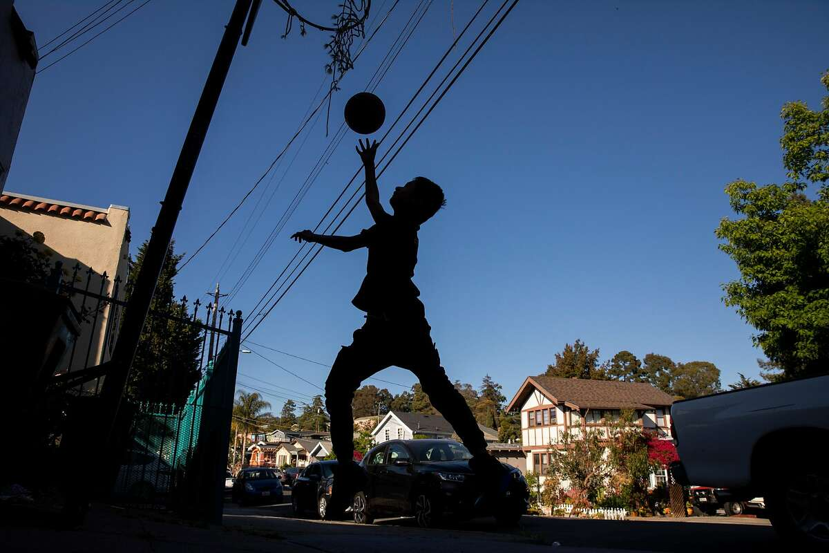 Angel Narvaez Cruz, 13, plays basketball outside his home along 25th Avenue in the Reservoir Hill neighborhood on Tuesday, May 4, 2021, in Oakland, Calif. His family has been living in the neighborhood for two decades.