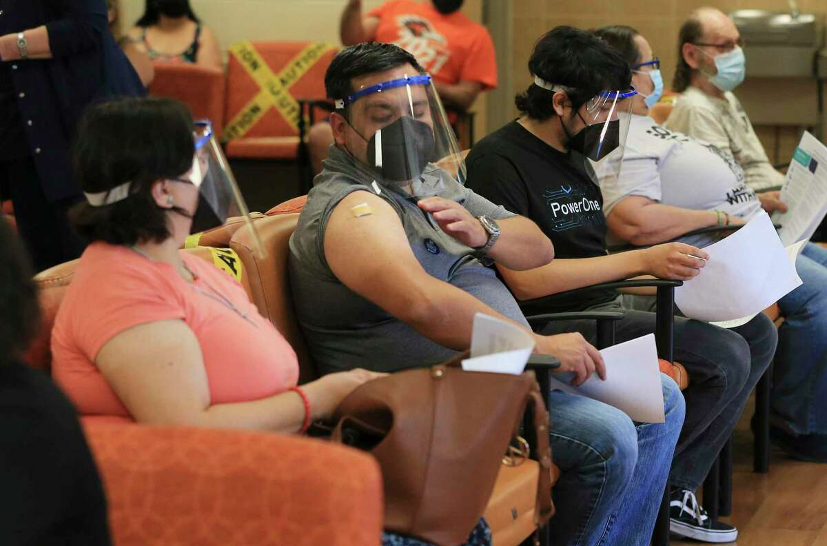 People sit and wait Wednesday after getting the J&J vaccine at the University Health Zarzamora Clinic.