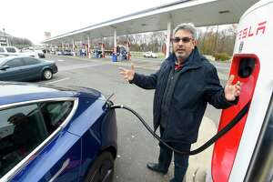 Ray Malkani, of Virginia, charges his Tesla vehicle at an Interstate 95 rest plaza on Nov. 27, 2019.