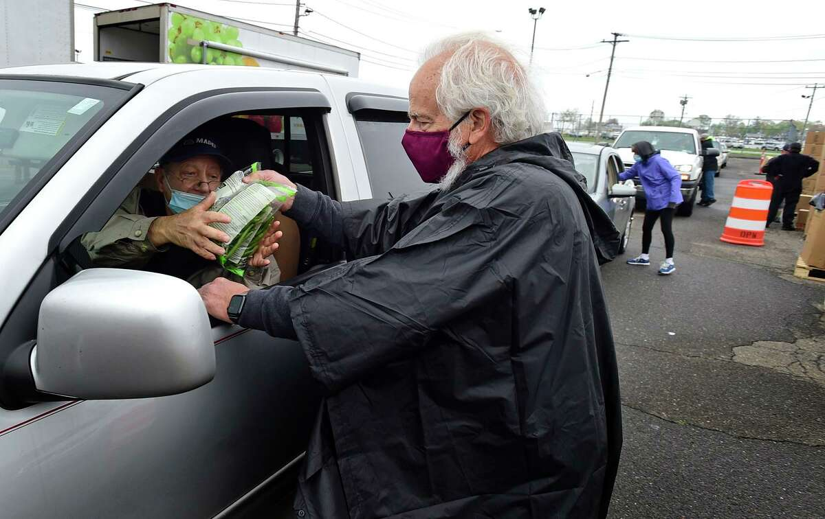 Volunteers including Norwalk resident Rick Wetzel, right, distribute food at the The weekly CT Food Bank program Wedmesday, May 5, 2021, at Veteran's Memorial Park in Norwalk, Conn. The weekly CT Food Bank program has moved from Calf Pasture to Vets Park.
