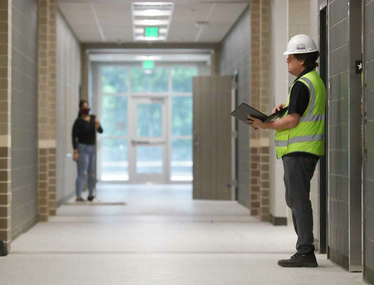 A worker tests hallway lights during a tour of the nearly completed Ruben Hope Elementary, Wednesday, May 5, 2021, in Grangerland. The Caney Creek High School feeder school, named after the former Conroe ISD board member and state representative, will open with 450 students this fall with a full capacity of 1,000 students for grades pre-k through 4th grade.