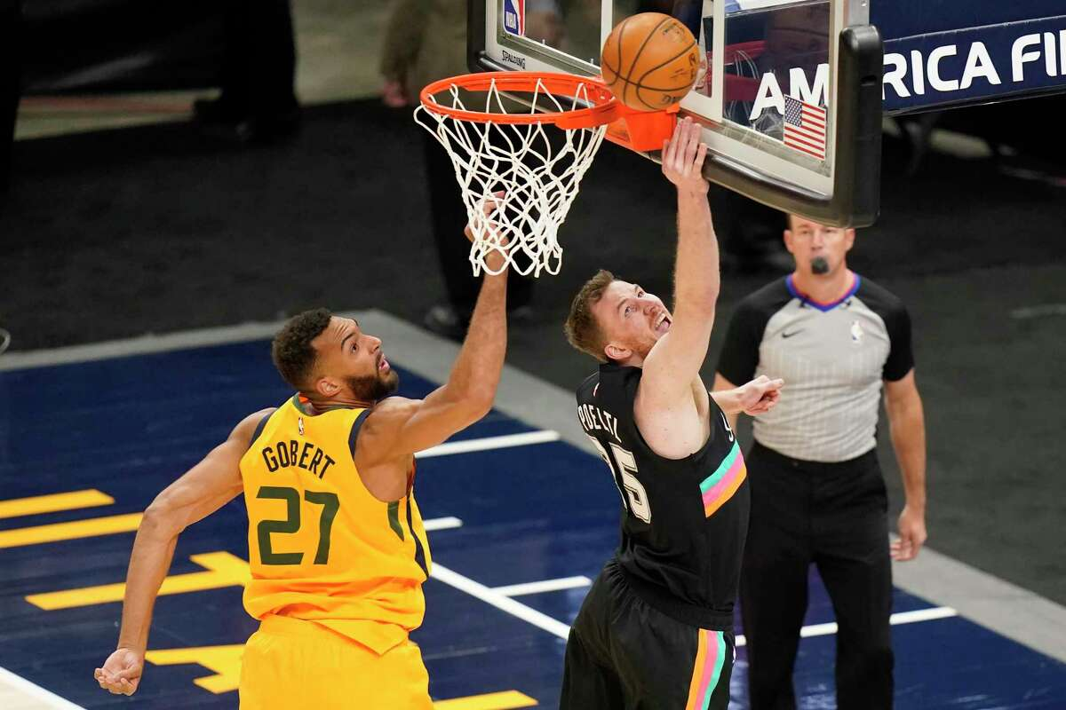 San Antonio Spurs center Jakob Poeltl (25) lays up the ball as Utah Jazz center Rudy Gobert (27) defends in the first half during an NBA basketball game Monday, May 3, 2021, in Salt Lake City. (AP Photo/Rick Bowmer)